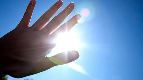 Close-up of hand in front of blue sky with burning sun --- Image by ?beyond/Corbis